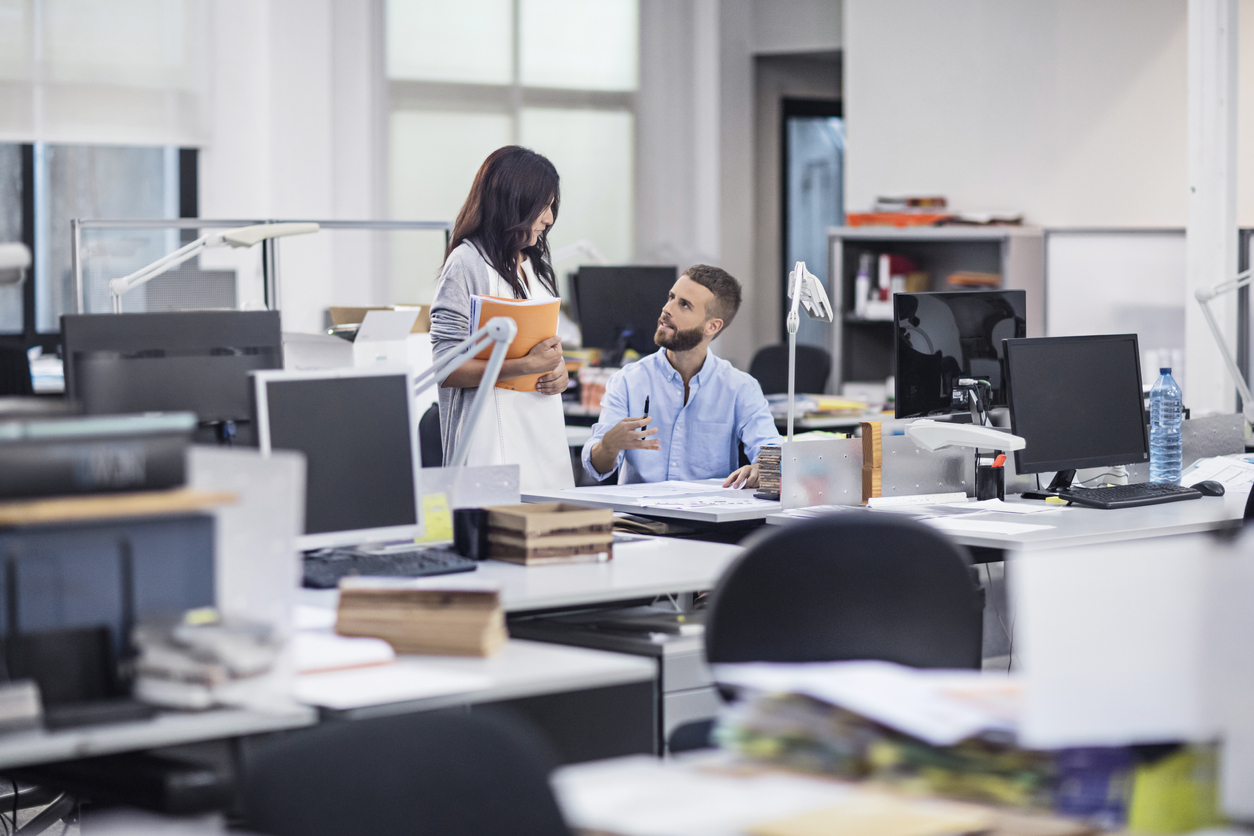 Business colleagues discussing at desk in office. Creative male and female professionals are planning strategy at workplace. They are in smart casuals.