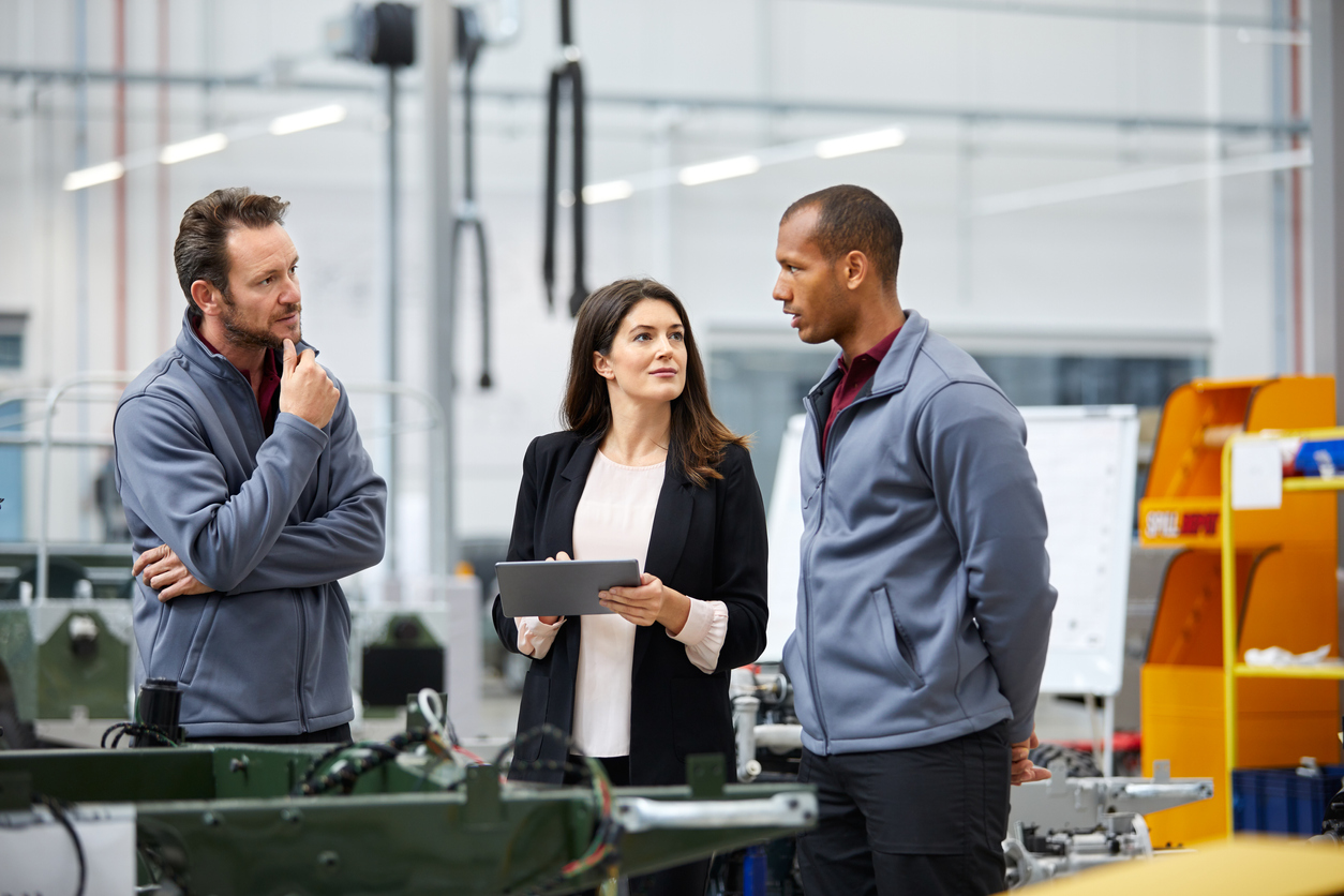 Automobile engineer discussing with colleagues in car factory. Multi-ethnic male and female professionals are standing at car production line. They are in automotive industry.