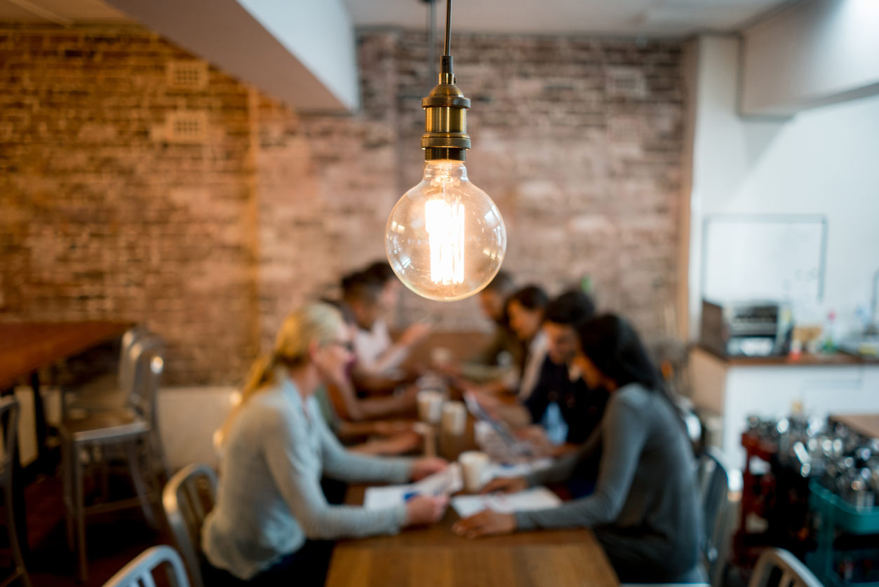 Group of business people brainstorming at a creative office and a light bulb in the foreground